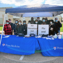 A group of volunteers wearing masks and winter coats stands under a tent behind blue Penn Medicine tablecloths, holding signs that say FIT Education and Test, and Flu and FIT
