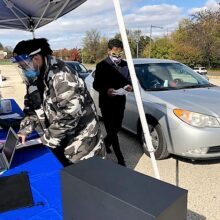 Two masked volunteers stand under a pop-up tent as a car passes by at Flu-FIT fair outside Enon Tabernacle Church.