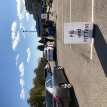 """A large white sign says """"Flu and FIT Test"""" next to a row of cars approaching a blue pop-up tent in a parking lot."""