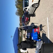 A row of cars passes a blue tent i a parking lot on a late fall day. A volunteer is leaning toward the passenger window of one car, holding a white envelope with a FIT kit.